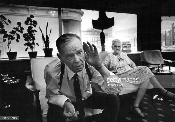 Raymond J Ellis clips his hand to his ear to question as he sits in lobby with Mrs Carolene Atkins Credit Denver Post