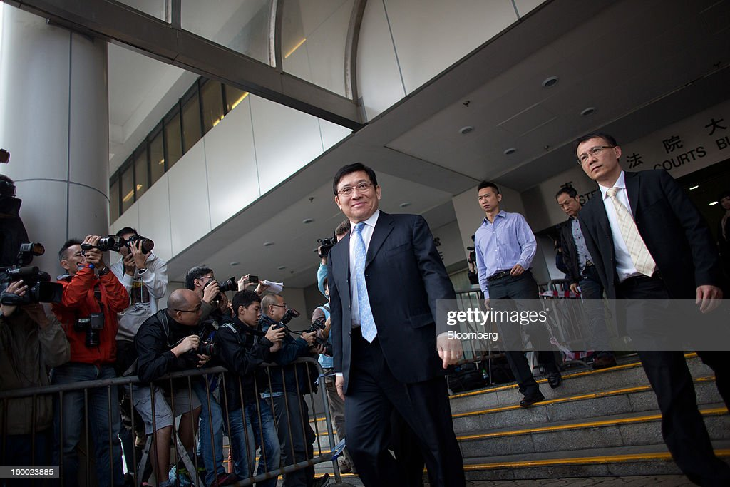 Raymond Kwok, co-chairman of Sun Hung Kai Properties Ltd., center, exits the Eastern Magistrates' Court in Hong Kong, China, on Friday, Jan. 25, 2013. The prosecution's bribery case against Sun Hung Kai's billionaire co-chairmen Thomas and Raymond Kwok and Hong Kong's former No. 2 official Rafael Hui will be ready by March, a court was told. Photographer: Lam Yik Fei/Bloomberg via Getty Images