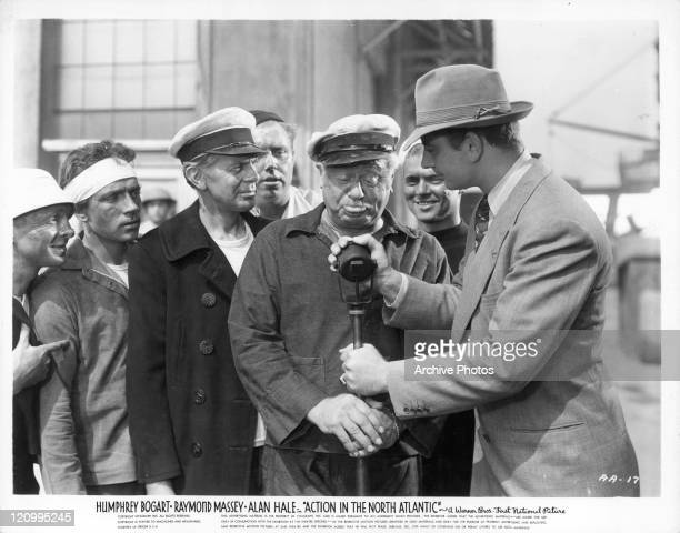 Raymond Massey among unidentified men in front of microphone in a scene from the film 'Action In The North Atlantic' 1943