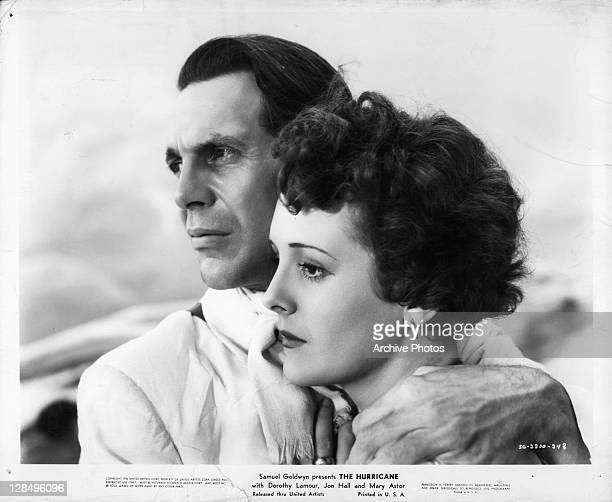 Raymond Massey with arms around Mary Astor in a scene from the film 'The Hurricane' 1937