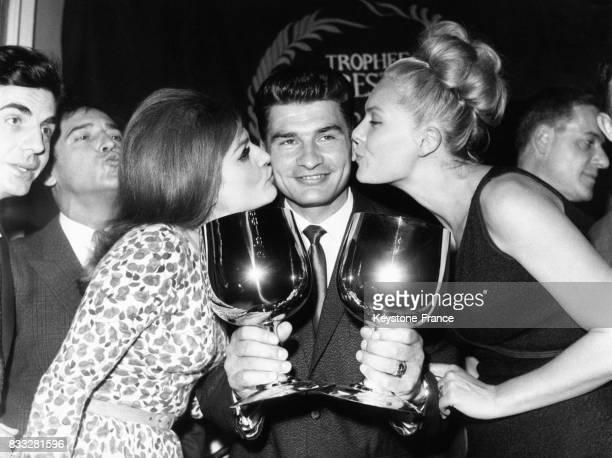 Raymond Poulidor tenant ses deux coupes est félicité par Dalida et Corinne Marchand en France le 18 novembre 1964