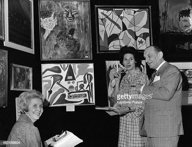 Raymond Rodel montre son tableau 'Grandes Lignes' a la Baronne Alix de Rothschild et a la Baronne Alain de Gunzburg respectivement presidente et...