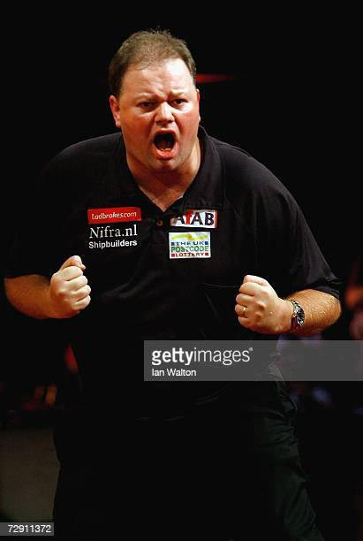 Raymond Van Barneveld of Holland celebrates a point against Phil Taylor of England Britain during the finals of the Ladbrokes World Darts...