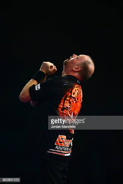 Raymond van Barneveld of Holland celebrates a set point in his third round match against Michael van Gerwen of Holland on Day Eleven of the 2016...