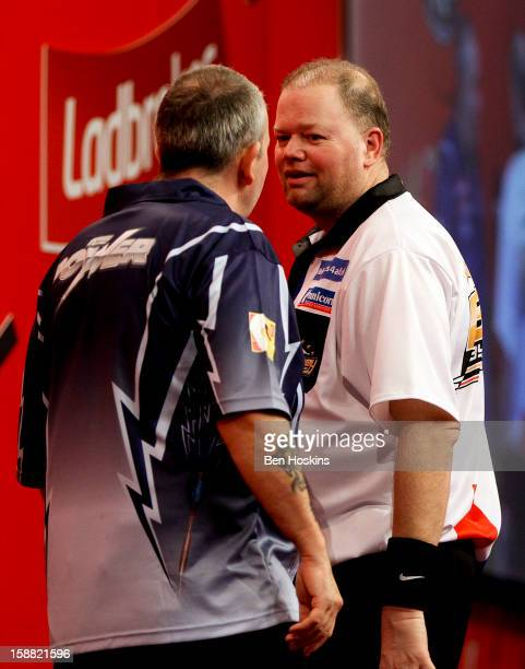 Raymond van Barneveld of the Netherlands and Phil Taylor of England clash during their semi final match on day fourteen of the 2013 Ladbrokescom...