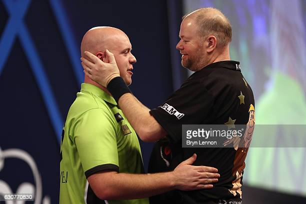 Raymond van Barneveld of The Netherlands congratulates Michael van Gerwen of The Netherlands on winning their semifinal match on day fourteen of the...