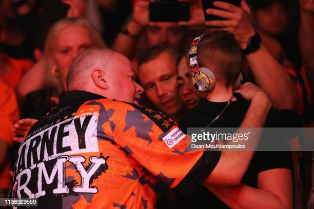 Raymond van Barneveld of the Netherlands shows some emotions with his family before he competes against Michael van Gerwen of the Netherlands during...