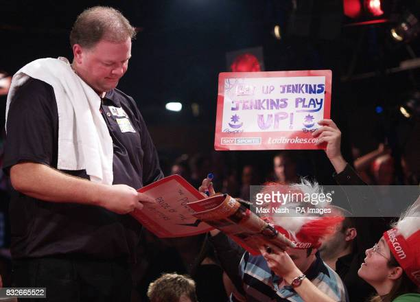 Raymond van Barneveld of the Netherlands signs autographs for England's Andy Jenkins fans after winning their Semifinal match 60 in the World Darts...