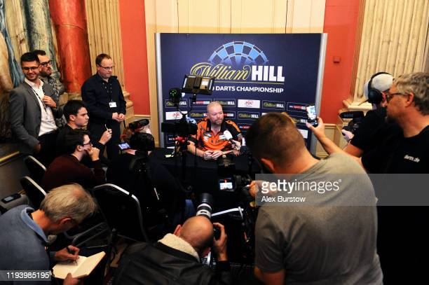 Raymond van Barneveld of The Netherlands speaks to the media after loosing his First Round match against Darin Young of The United States during Day...