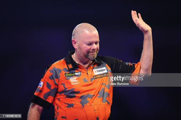 Raymond van Barneveld of The Netherlands waves to the fans as he walks off the stage after loosing his First Round match against Darin Young of The...
