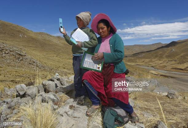 Raymunda Charca helps her tenyearold son Alvaro Cabrera as he searches for signal on top of a hill in order to attend a virtual class during the...