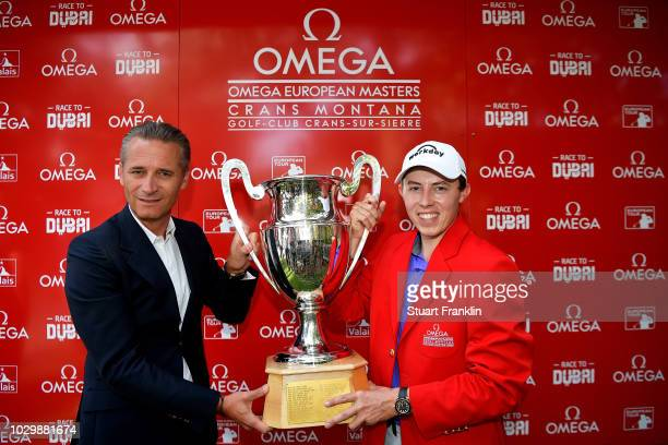 Raynald Aeschlimann president of Omega hands the trophy to Matthew Fitzpatrick of England during day four of The Omega European Masters at...
