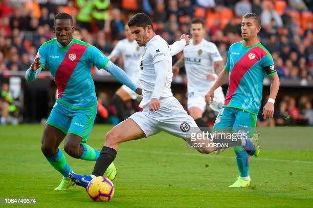 Rayo Vallecano's Peruvian defender Luis Advincula challenges Valencia's Portuguese midfielder Goncalo Guedes during the Spanish league football match...