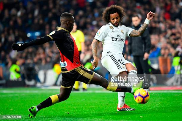 Rayo Vallecano's Peruvian defender Luis Advincula vies with Real Madrid's Brazilian defender Marcelo during the Spanish League football match between...