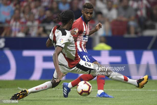 Rayo Vallecano's Senegalese defender Abdoulaye Ba vies with Atletico Madrid's French midfielder Thomas Lemar during the Spanish league football match...