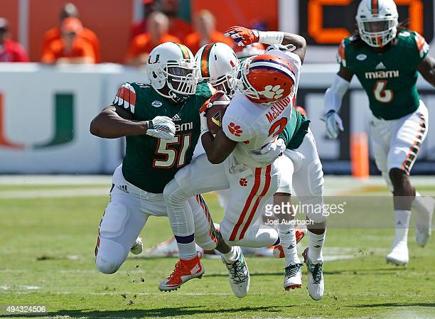 Ray-Ray McCloud of the Clemson Tigers is tackled by Juwon Young and Corn Elder of the Miami Hurricanes during first quarter action on October 24,...
