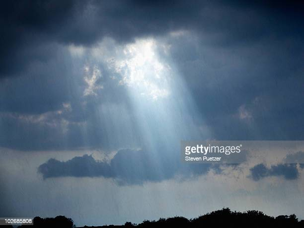 Rays of light coming through clouds as rain falls