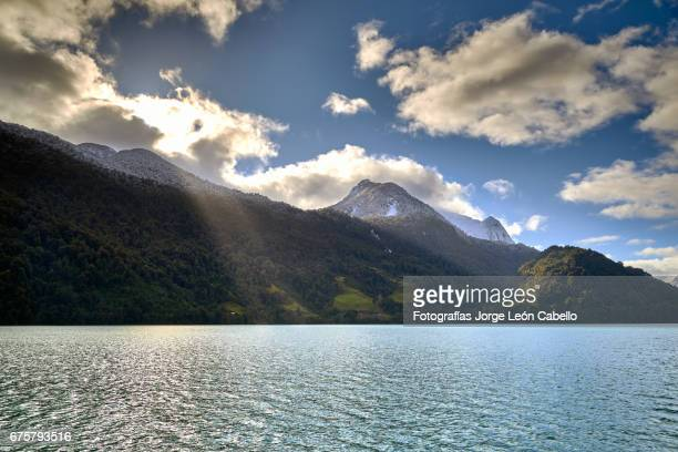 rays of light falling from the mountains during the winter andean lake crossing - azul turquesa stockfoto's en -beelden