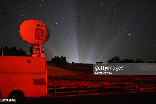 Rays of light from inside Neverland Ranch shine among the stars in the early morning darkness behind a television news satellite truck that is...