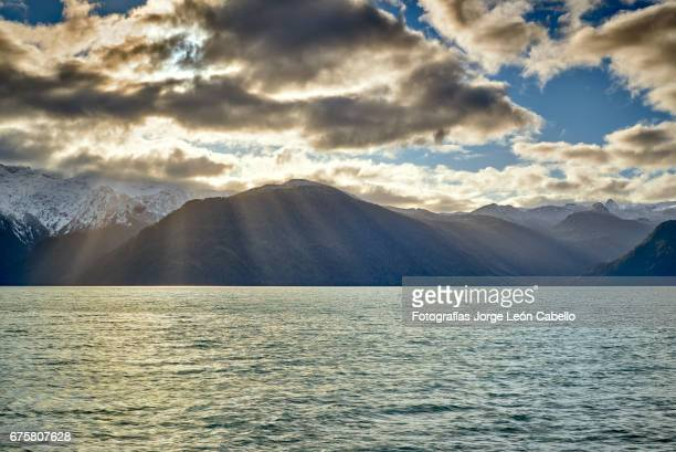 rays of light over the andes range view during the andean lake crossing - azul turquesa stockfoto's en -beelden