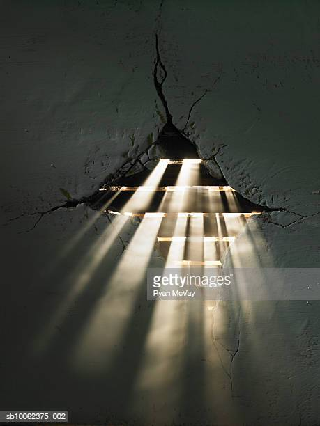 Rays of light shining through hole in wall