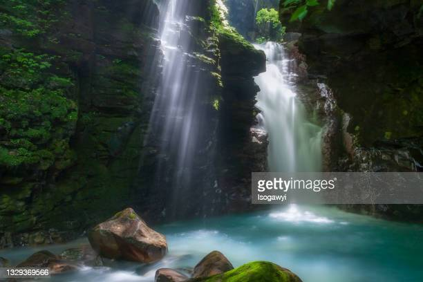 rays of sunlight into deep ravine with waterfalls - isogawyi stock pictures, royalty-free photos & images