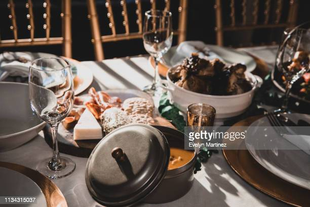 rays of sunlight on dinner table set up. empty glasses and napkin wrapped flatware on dinner plates. metal tin container of beans (habichuelas). out of focus: chicken and appetizers. partial view of chairs in the upper section of photo. - evelyn martinez stock pictures, royalty-free photos & images