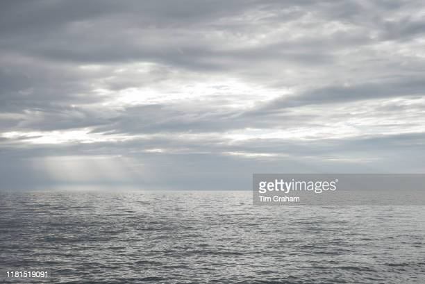 Rays of the sun breaking through dark cloud above the Atlantic Ocean at sunset in Wales United Kingdom