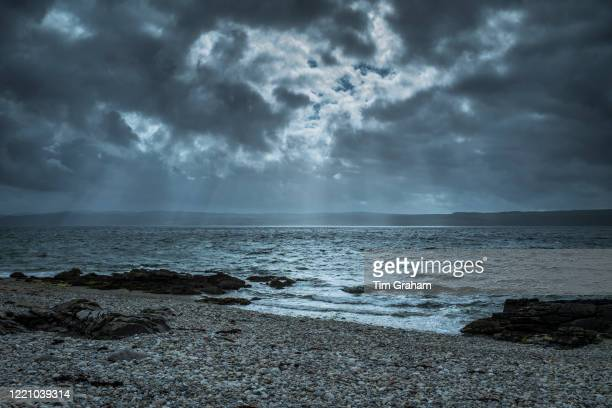 Rays of the sun breaking through dark clouds over the seashore on northern coast of the Isle of Arran Scotland