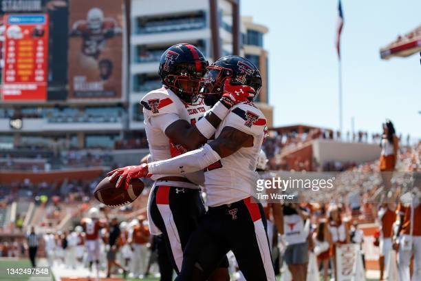 Rayshad Williams of the Texas Tech Red Raiders congratulates Dadrion Taylor-Demerson after an interception in the end zone in the third quarter...