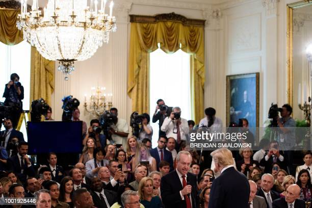 Raytheon CEO Tom Kennedy speaks to US President Donald Trump during a job creation pledge event in the East Room of the White House July 19 2018 in...