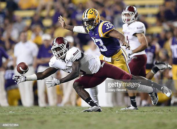 Rayvean Moore of the New Mexico State Aggies reaches for a pass in front of Jamal Adams of the LSU Tigers during the third quarter of a game at Tiger...