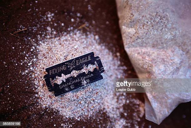 A razor blade used in traditional female circumcision ceremonies sits on a pile of millet flour which is used to stop the bleeding While a...