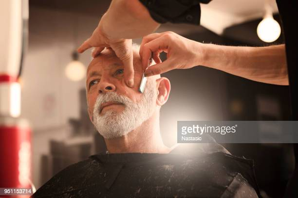 razor in hands of specialist barber - barber stock pictures, royalty-free photos & images