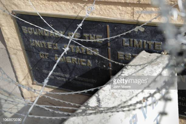 Razor wire and a concrete barrier stand in front of the USMexico border marker after US officials reopened the San Ysidro port of entry on November...