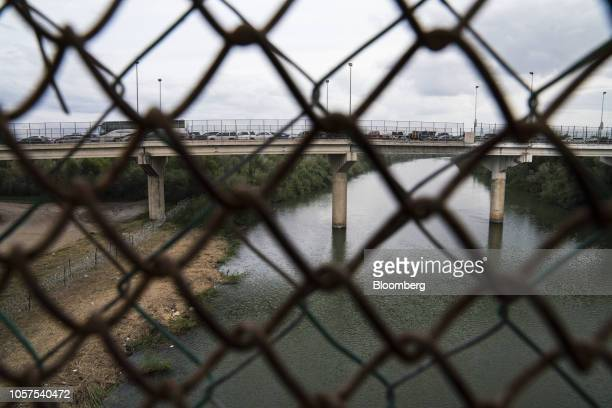 A razor wire fence standing along the Rio Grande river and vehicles sitting in traffic on the McAllenHidalgoReynosa International Bridge are seen...