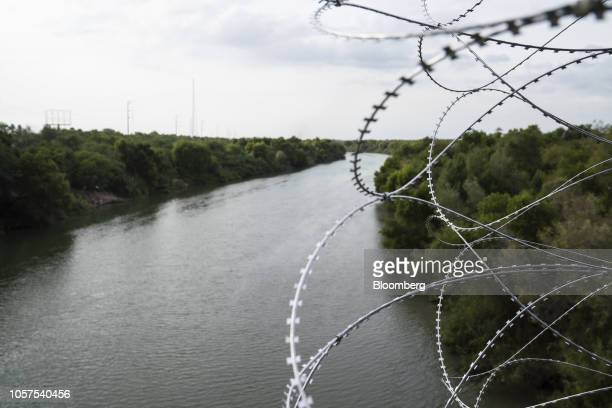 Razor wire fencing hangs from the McAllenHidalgoReynosa International Bridge above the Rio Grande river in Hidalgo Texas US on Sunday Nov 4 2018...