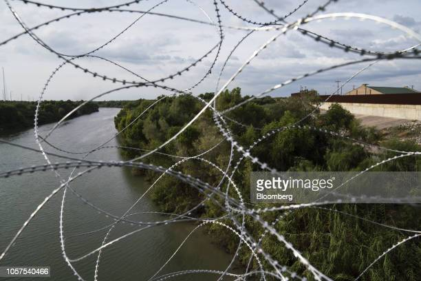 Razor wire fencing hangs from the McAllenHidalgoReynosa International Bridge above the Rio Grande river in Hidalgo Texas US on Sunday Nov 4 2018...