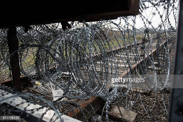 Razor wire sits coiled by security fence blocking a railway line on the HungarianSerbian border near Roszke Hungary on Wednesday Feb 17 2016 The...