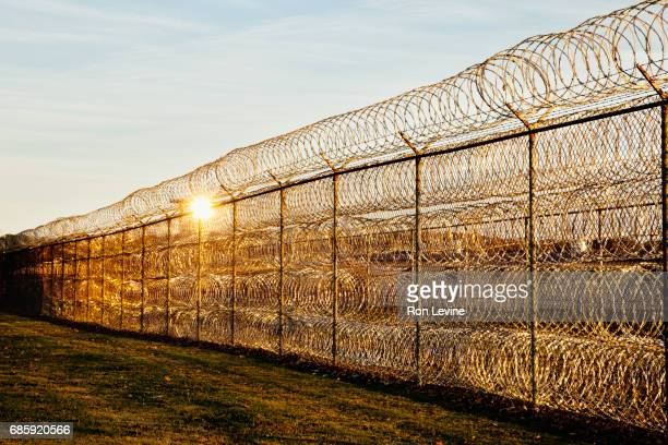 razor wire surrounding a prison - louisiana stock photos and pictures