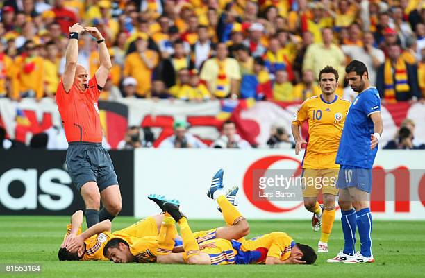 Razvan Rat , Paul Codrea and Mirel Radoi of Romania all lie on the ground after a collision as referee Tom Henning Ovrebo of Norway signals to the...