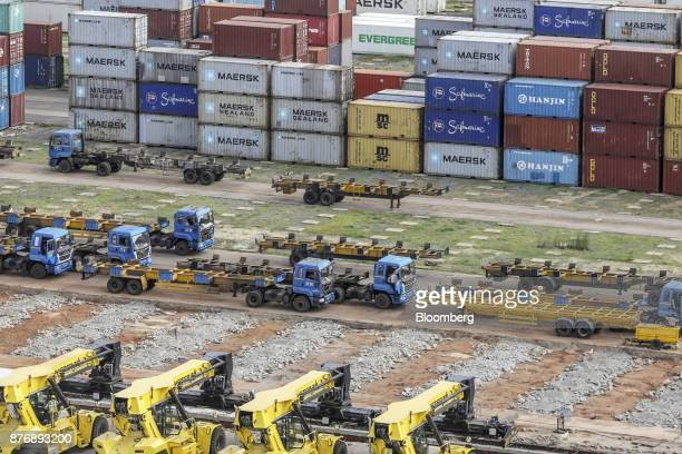 Reach stackers and trucks sit parked near containers stacked in a yard at Krishnapatnam Port in Krishnapatnam Andhra Pradesh India on Saturday Aug 12...