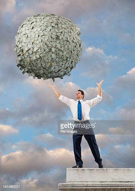 reaching for big ball of money - man with big balls stock photos and pictures