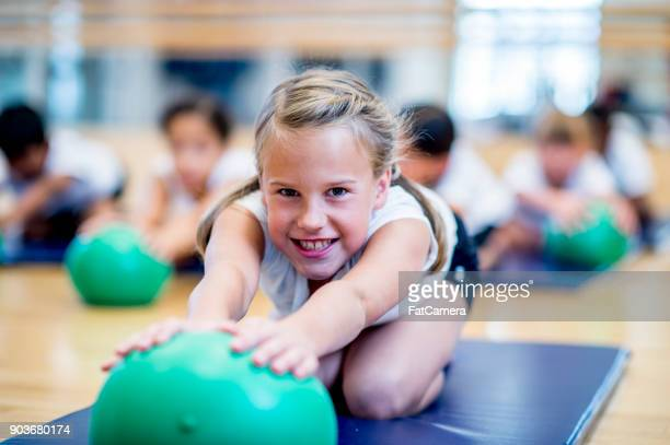 reaching for exercise ball - physical education stock photos and pictures