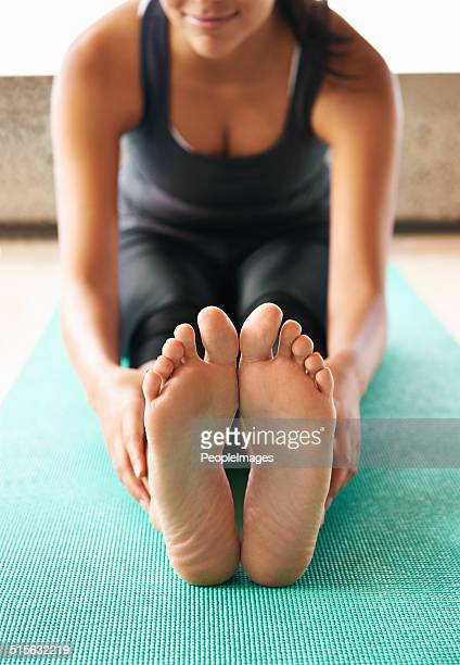 reaching for those toes - female feet soles stock photos and pictures