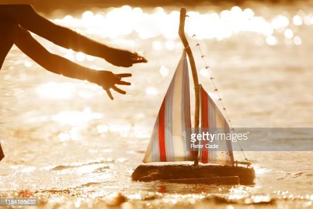 reaching for toy boat on the water at sunset - loslassen aktivitäten und sport stock-fotos und bilder