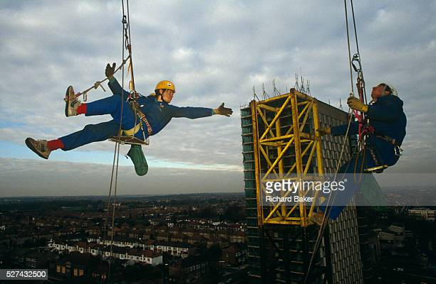 Reaching out to a tower of scaffolding high above the skyline of North London a member of a company of abseiling construction scaffold workers make...