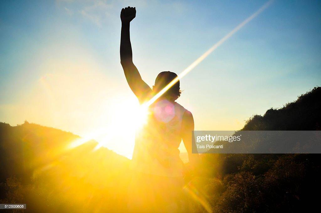 Reaching the glory - man rising his fist : Stock Photo