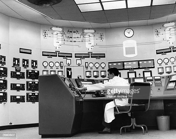 A reactor controller sitting at the instrument panel in AGR control room at Windscale nuclear power station