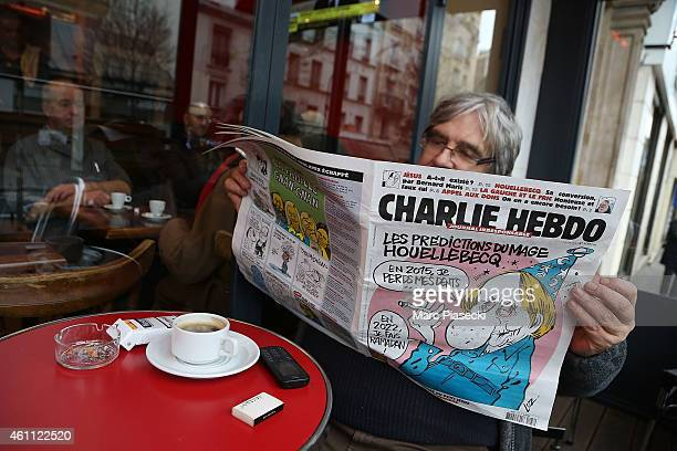 A reader is seen with the 'Charlie Hebdo' newspaper in a Parisian cafe on January 7 2015 in Paris France Gunmen have attacked french satirical weekly...